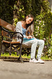 Smiling student sitting on bench and writing on notepad