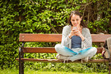 Smiling student sitting on bench text message on her mobile phone