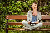 Smiling student sitting on bench listening music with mobile phone and holding book