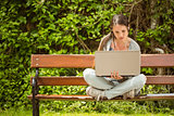 Student sitting on bench listening music and using laptop
