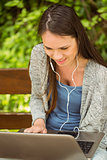 Smiling student sitting on bench listening music and using laptop
