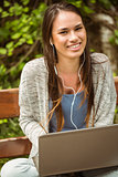 Smiling student sitting on bench listening music and holding laptop