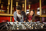 Smiling friends playing table football together