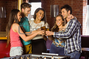 Portrait of happy friends toasting with mixed drink and beer