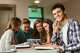 Smiling friends sitting studying and using tablet pc