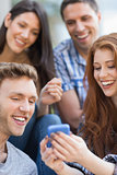 Happy students looking at smartphone outside on campus