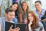 Happy students looking at book outside on campus
