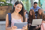 Pretty student using her tablet pc on campus