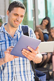 Happy student using his tablet pc on campus