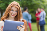Pretty student smiling at camera using tablet pc