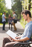 Handsome student studying outside on campus