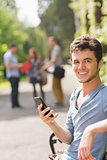 Handsome student sending a text outside