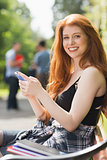 Pretty student sending a text outside