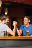 Happy friend arm wrestling each other