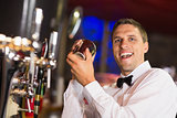 Handsome barman smiling at camera making a cocktail