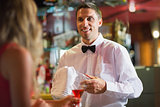 Handsome barman chatting to customer
