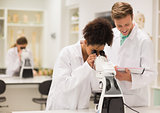 Medical students working with microscope