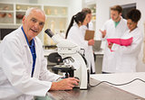 Smiling medical professor working with microscope