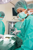 Medical student looking at camera during practice surgery