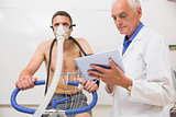 Doctor showing tablet pc to man doing fitness test
