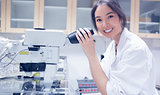 Pretty scientist smiling at the camera using microscope