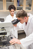 Young scientist working with microscope