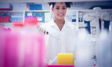Pretty science student using pipette