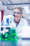 Happy science student working with microscope in the lab