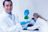 Science student holding green chemical in beaker