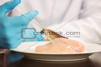 Food scientist injecting raw chicken