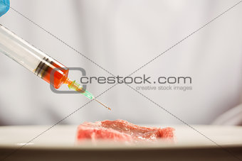 Food scientist injecting raw meat