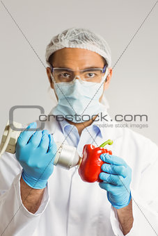 Food scientist using device on pepper