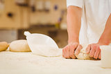 Baker kneading dough at a counter