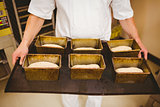 Baker holding tray of loaf tins