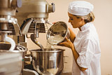 Baker pouring flour into large mixer