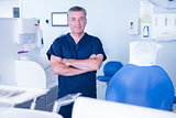 Dentist in blue scrubs smiling at camera