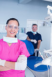 Smiling assistant and dentist behind her with protective glasses