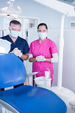 Dentist and assistant in surgical mask and protective glasses