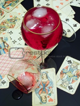 Broken glass, wine with ice and cards