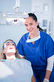Dentist smiling at camera with patient in the chair