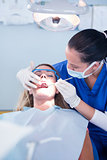 Dentist examining a patients teeth under bright light