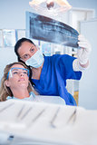 Dentist in mask explaining x-ray to patient