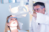 Dentist examining a patients teeth in chair under bright light