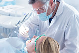 Dentist examining a patients teeth with surgical mask and gloves