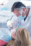 Dentist in surgical mask and gloves holding tool