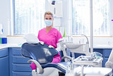 Dentist in mask looking at camera beside chair