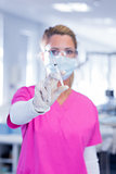 Dentist in surgical mask and scrubs holding syring