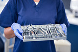 Dentist in blue scrubs holding tray of tools
