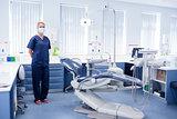 Dentist in blue scrubs standing beside chair