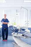 Dentist in blue scrubs standing with arms crossed